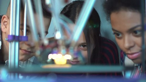 Close view of group of classmates watching after three-dimensional printing in contemporary laboratory. Static 4K shot on Red cinema camera.