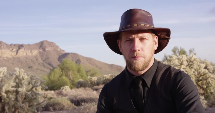 American Cowboy tips cowboy hat towards camera