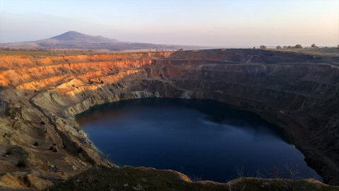 Sunset time-lapse of open pit copper mine. Mountain carved into terraces for mining and forming an artificial lake.