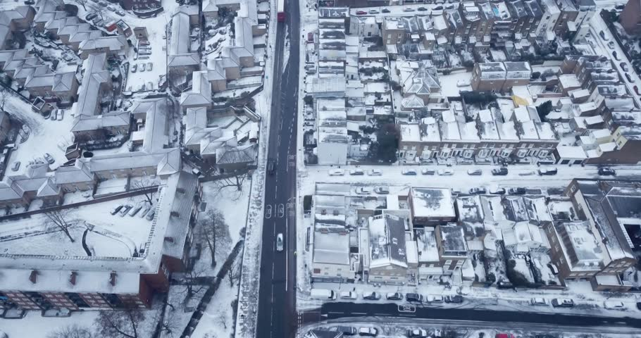 Top down Aerial Drone footage of South London, England during a snow storm March, 2018.  Cars and busses drive on main roads but small roads and roofs are all covered with fresh white snow.