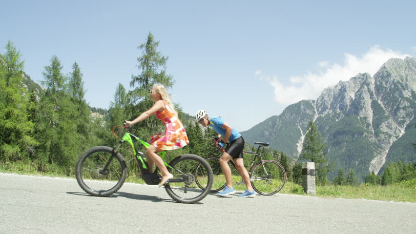 Pro biker gives up and walks along his road bicycle as blonde girl overtakes him effortlessly. Onlooking male biker stops and praises blonde woman pedaling up a steep hill on her cool electric bike. | Shutterstock HD Video #1008137620