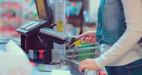 Customers buying food and staples from a cashier and paying at the till. Supermarket store. Close-up