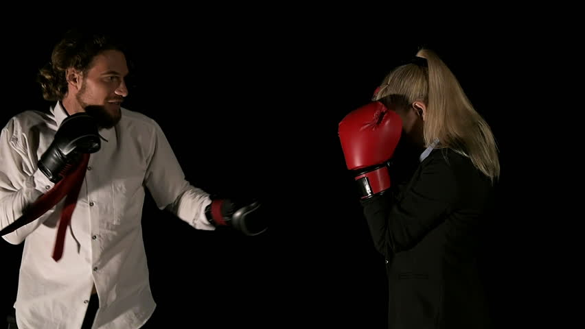 Young business woman blocking punches from her bully boss. Her male boss keep punching her. White young beautiful woman and white man. Shot in slow motion. Work place inequality concept.