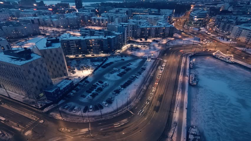 Sunset from day to night time lapse with traffic, buildings, city lights, frozen icy sea and winter snow. Jatkasaari, Ruoholahti, Halsinki, Finland | Shutterstock HD Video #1008171640