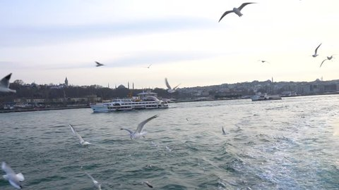 Walking ship moors in port against mosque Yeni Camii