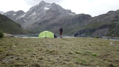 Drone shot, Man on a hike standing by its tent near a stunning mountain lake in the heart of the French Alps. Man hiker standing in nature arms outstretched. Young male arms wide open in the European
