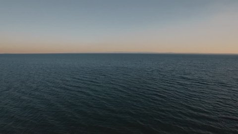 Flying over deep rippling sea at sunset. Vast blue water space and skyline