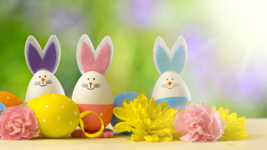 Cute Easter bunny ornaments and Easter Eggs on white table against garden background in the breeze, panning with lens flare.