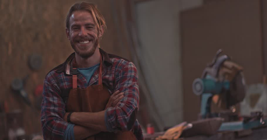Portrait of small business owner carpenter smiling and standing in industrial furniture manufacturing workshop