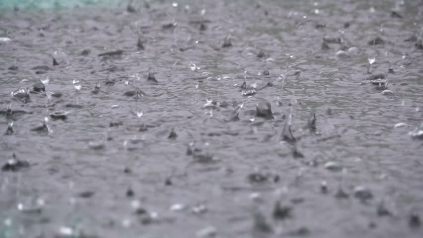 Large Drops of Rain fall in a Puddle During a Rainstorm. Slow Motion in 96 fps. Water Drops. Close-up. Heavy rain fall background.