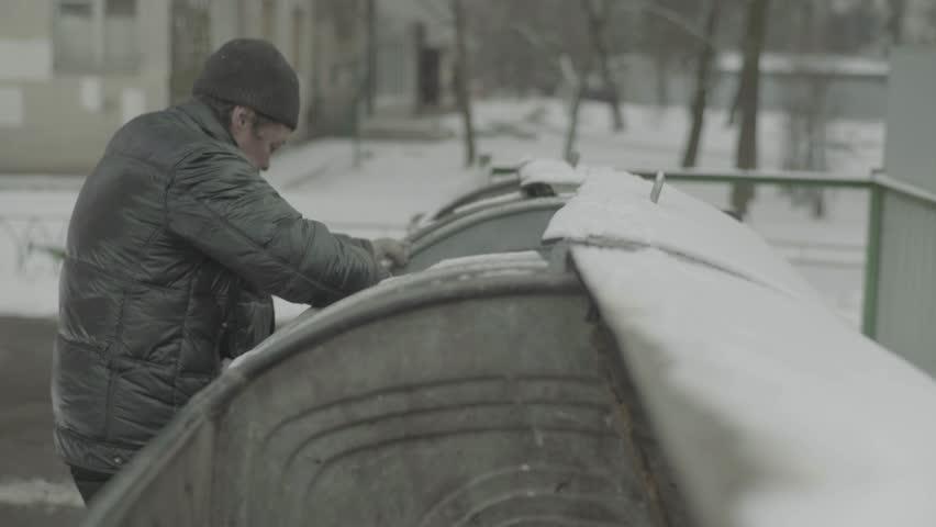 Beggar man digs in the trash | Shutterstock HD Video #1008235270