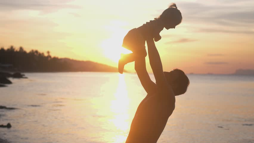 Happy father and daughter playing on the beach at amazing sunset with lens flare effects. Dad holds cute girl in hands. slow motion. 3840x2160 #1008257500