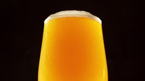 Glass of beer turns slowly around its axis. Beer bubbles rise to the beer foam. Close up 4K video. Black background.