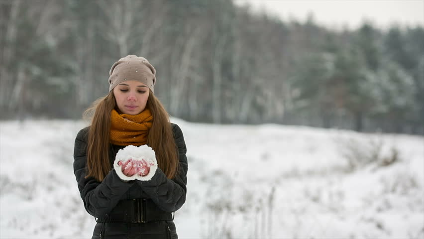 Smiling girl picking up snow. She blows it off with her palms and throwing up snow, snowflakes falling on female hair and face. Red-haired lady with long hair wearing black coat and scarf standing on