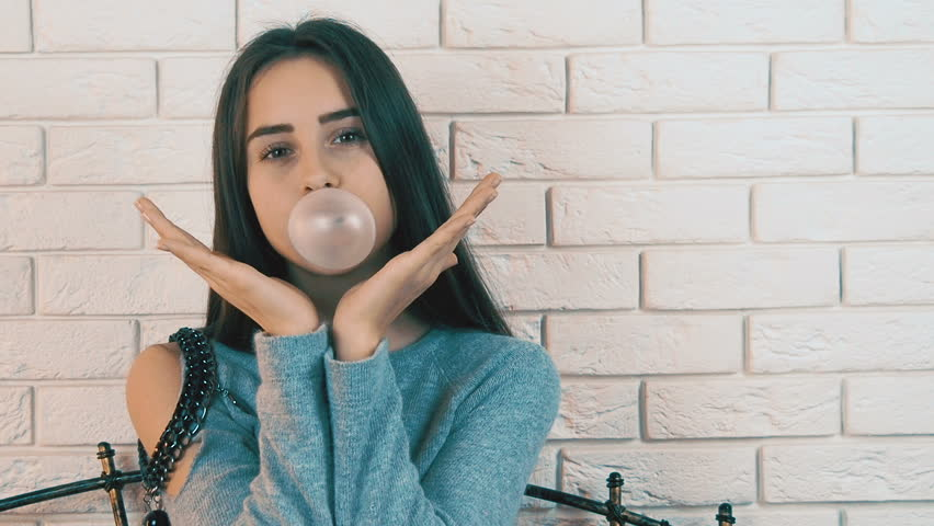 A girl with a chewing gum blows a bubble.
