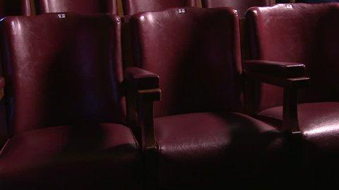 A scenic gliding shot of empty seats in a movie theatre.