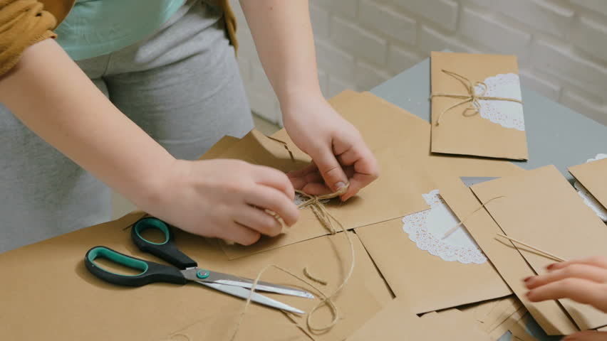 Professional woman decorator, designer working with kraft paper and wrapping envelope at workshop, studio. Decorating, handmade and art concept