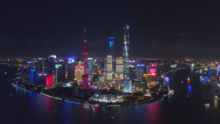 SHANGHAI, CHINA - MAY 5, 2017 Aerial drone video, night time illuminated famous pudong cityscape, business finance centre skyscrapers skyline, Huangpu river , historical and modern architecture, Bund