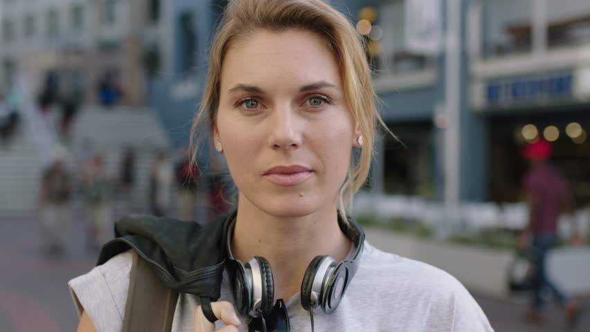 Portrait of independent blonde woman looking serious staring intense wearing headphones on urban city background confident self-assured | Shutterstock HD Video #1008347020