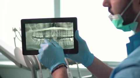 Intelligent dentist showing teeth x-ray on tablet, well-built man in green mask and blue gloves explaining particular case, sitting before dental chair in light huge office