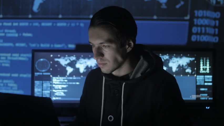 Young Geek Hacker programmer is working on computer in cyber security center filled with display screens. | Shutterstock HD Video #1008364960