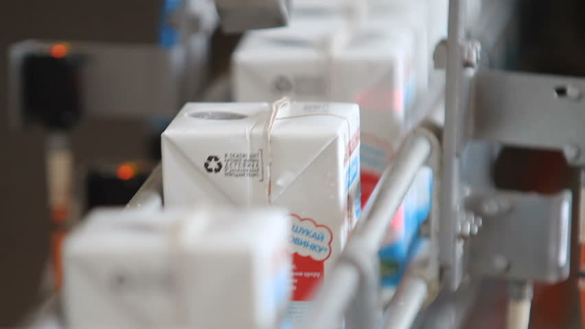 Kiev Region, Ukraine - Februry 2017: Milk packaging line. Dairy products in tetra packaging are moving along the conveyor at a dairy factory. Tetra baby food packaging.