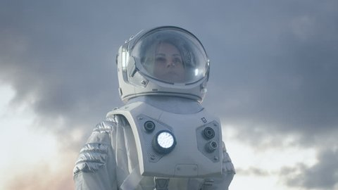 Low Angle Shot of Female Astronaut in the Space Suit Looking Around Alien Planet. Blue and Cold Planet. Advanced Technologies, Space Travel, Colonization Concept. Shot on RED EPIC-W 8K Helium Camera.