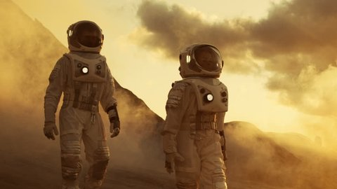 Two Astronauts in Space Suits Confidently Walking on Mars, Exploration Expedition on the Planet's Surface. Red Planet Covered in Rocks, Gas and Smoke. Humans Overcoming Difficulties. 4K UHD.