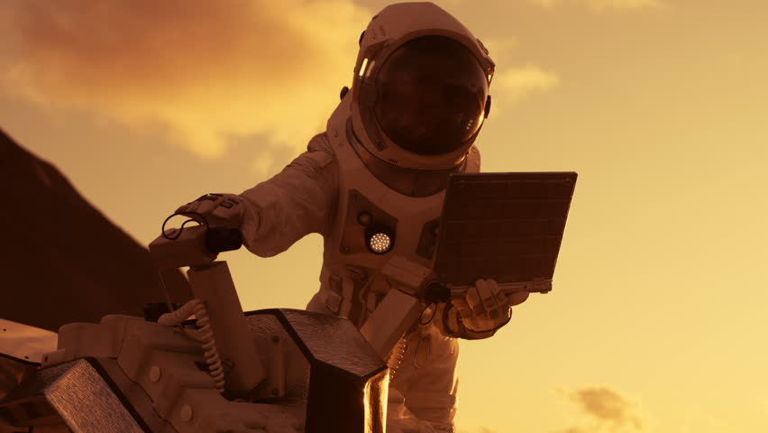 Astronaut in the Space Suit Works on Laptop, Adjusting Rover For Mars further Mars Exploration.Space Exploration Concept.First Manned Mission on Red Planet. Shot on RED EPIC-W 8K Helium Cinema Camera.