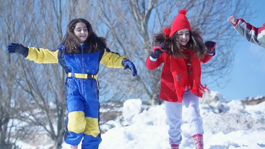 Three kids run and jump on snow as they laugh. Mount Lebanon, Lebanon