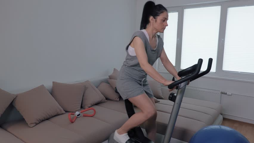 Woman do exercises on stationary bicycle
