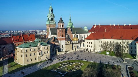 Royal Wawel Gothic Cathedral in Cracow, Poland, with Renaissance Sigismund Chapel with golden dome,  Wawel Castle, yard, park and tourists. Aerial 4K reveal video at sunset