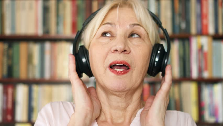 Cheerful funny silly senior woman listening music with big black wireless headphones. Positive pensioner meloman singing to music. Active modern life after retirement.