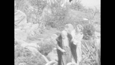 1930s: Women walk up steps, older woman holds younger woman's hand, pulls her along. Woman talks. Women and men walk down steps.