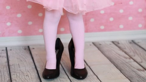 A child in adult shoes on a pink background. Glamor. Fashion. Girl fashionista. Baby legs in mother's shoes. Black female shoes with heels. Close-up.
