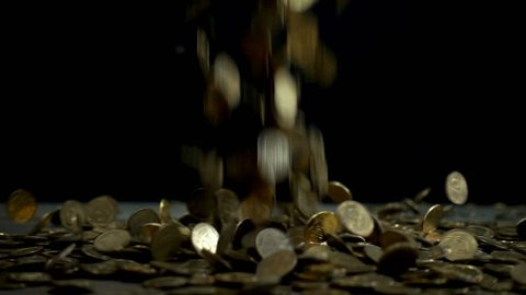 Slow motion, a pile of coins falls on a wooden table on a black background. Ukrainian pennies are falling a heap