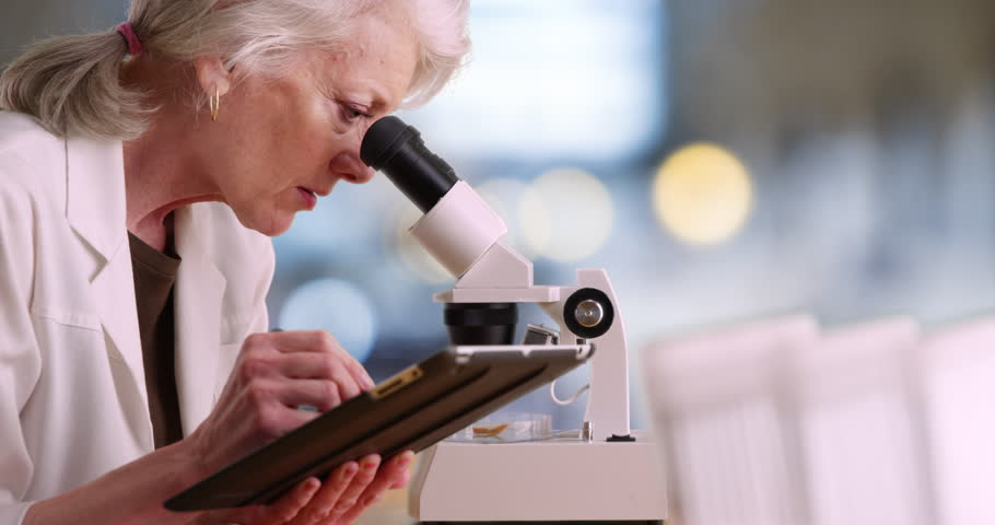 Mature female scientist working alone in lab takes notes on tablet computer and looks into microscope. Senior woman using pad to do medical research. 4k