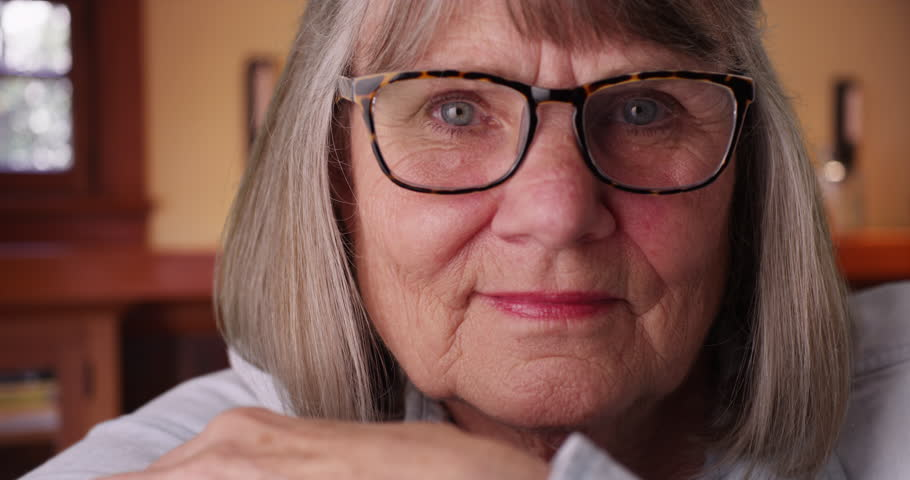 Close-up of somber elderly woman wearing eyeglasses looking at camera indoors. Close view of relaxed senior lady's face looking at camera in her living room. 4k