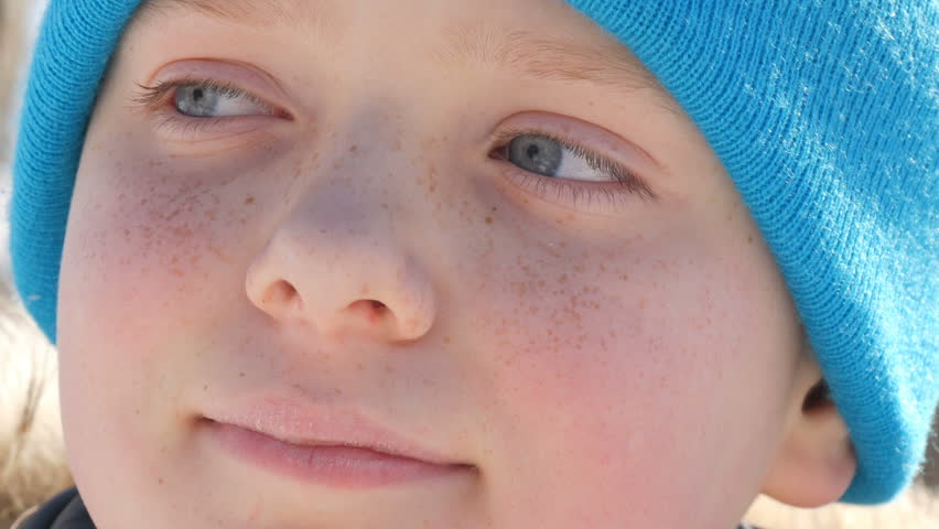 Boy teenager with sky blue eyes and freckles on his face in a blue hat looks into the distance   Shutterstock HD Video #1008538150