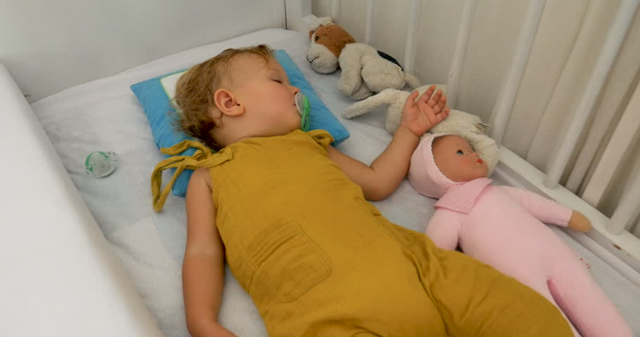 Sleeping baby infant lying in a crib with a pacifier in his / her mouth and toys in the bed