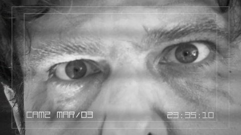 A CCTV screen recording: a threatening old man - a zombie - comes very close to the camera, his mouth wide open, ready to eat the viewer. Disturbing, scary, spooky shot.