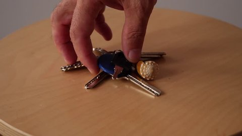 Taking Keys to little table and Taking them from table . Arriving / Leaving Home concept.Slow motion.