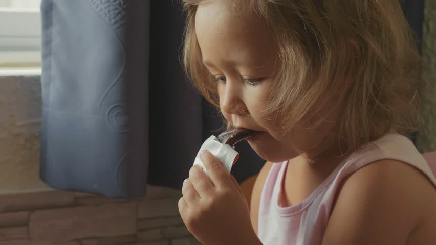 Portrait of little cute child girl watching something in the tablet and eats fruit snack bar next to window at living room, close-up. | Shutterstock HD Video #1008591220