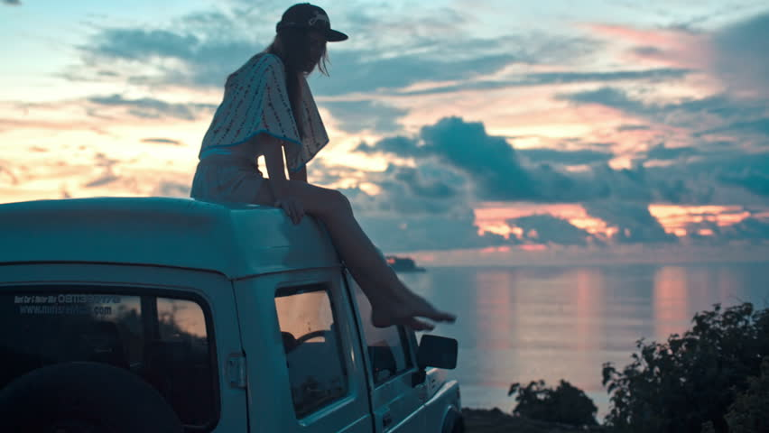 BALI, INDONESIA - DECEMBER 2017: Rear view of young woman sitting on car parked in front of ocean enjoying sunset #1008604030