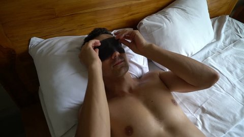 Young happy man waking up putting off his sleep mask blindfold stretching and looking around in bed in the morning in hotel room, holidays travel concept, ready for adventures