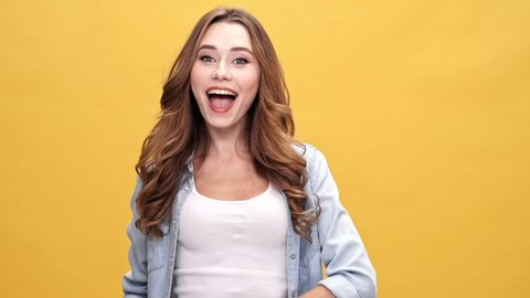 Funny brunette woman in denim shirt amusing and looking at the camera over yellow background