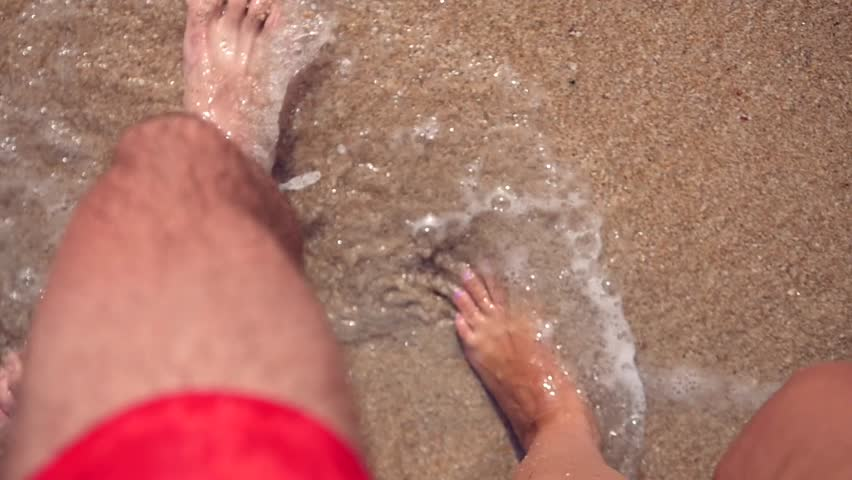 Two pairs of legs, a man and a woman pacing along the sandy beach, waves hit their feet, forming foam and bubbles. slow motion, 1920x1080, full hd | Shutterstock HD Video #1008655390