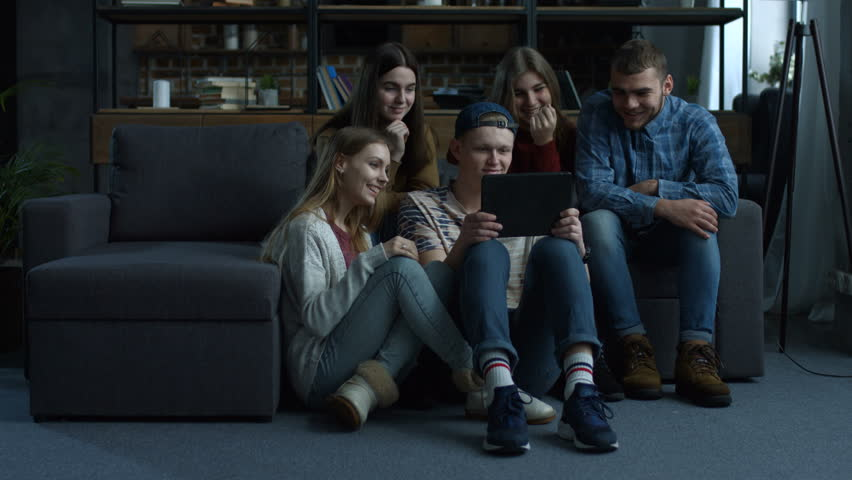 Group of cheerful young friends grouped around tablet computer and watching media content as they sit together in domestic room. Joyful hipster teenagers using digital tablet pc at home.   Shutterstock HD Video #1008668890