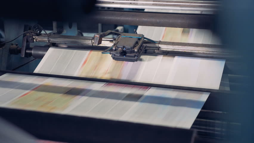 Uncut printed paper sheets are being processed by industrial equipment and moving along it in an upward direction | Shutterstock HD Video #1008697480