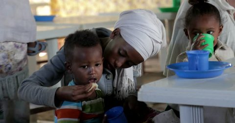 GONDAR, ETHIOPIA - JANUARY 18, 2017: Ethiopia Gondar african poor mother feed her sun poverty village people